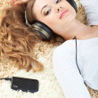 Woman lying on carpet and listening to music — Stock Photo