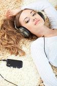 Kobieta leży na dywanie i słuchania muzyki — Zdjęcie stockowe