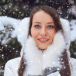 Beautiful brunette woman standing under snowfall - Stock Photo