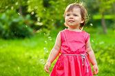 Klein meisje in het park met bubbels — Stockfoto