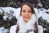 Beautiful brunette woman standing under snowfall — Stock Photo
