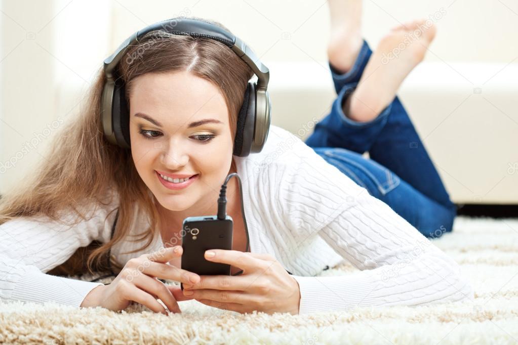 Frau liegend auf Teppich und Musik hören — Stockfoto