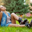 Girl wearing roller skates sitting on grass — Stock Photo