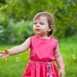 Little girl at park with bubbles — Stock Photo