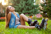 Dívka, která nosí kolečkové brusle sedí na trávě — Stock fotografie