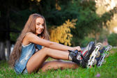 Girl sitting on the grass and puts on skates — Stock Photo