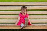Little girl sitting on bench — Stock Photo