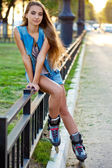 Roller girl wearing jeans sitting on iron fence — Stock Photo