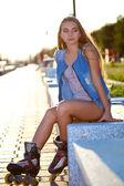Rolki dziewczyna dzinsach, siedząc na ławce — Zdjęcie stockowe