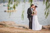 Bridal couple standing near lake — Stockfoto