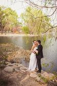 Bridal couple standing near lake — Stock Photo