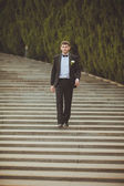 Groom walking on staircase — Stock Photo