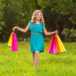 Happy woman at park with shopping bags — 图库照片