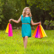 Happy woman at park with shopping bags — Stock Photo #28707005