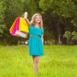 Happy woman at park with shopping bags — Stock Photo #28707011