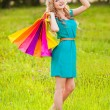 Happy woman at park with shopping bags — Stock Photo #28707033