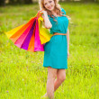 Happy woman at park with shopping bags — Stock Photo #28707035