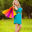 Happy woman at park with shopping bags — Stock Photo #28707049