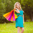 Happy woman at park with shopping bags — Stock Photo #28707053