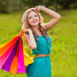 Happy woman at park with shopping bags — Stock Photo