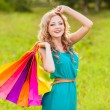 Happy woman at park with shopping bags — Стоковая фотография