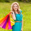 Happy woman at park with shopping bags — Stock Photo #28707107
