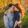 Couple kissing standing outdoos among bushes — Stock Photo