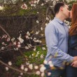 Couple kissing among the flowering trees — Stock Photo