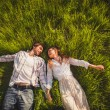 Couple in love lying on grass — Stock Photo