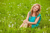 Woman sitting on filed with dandelions — Stock Photo