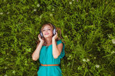 Woman laying on grass with headphones — Stock Photo