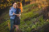 Couple kissing standing outdoos among bushes — Stock Photo