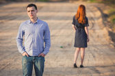 Sad man and woman stand on the dirt road — Stok fotoğraf