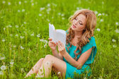 Serious woman reading book outdoors — Stock Photo