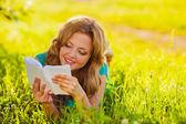 Glad kvinna läsa bok utomhus — Stockfoto