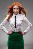 Red-haired businesswoman portrait over gray — ストック写真
