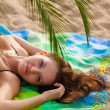 Woman wearing bikini lying on cover — Stock Photo