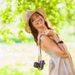 Happy young girl with camera outdoors — Stock Photo #30797539