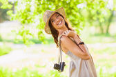 Happy young girl with camera outdoors — Стоковое фото