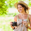 Happy young girl with camera outdoors — Stock Photo #30802429