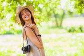 Happy young girl with camera outdoors — Stock fotografie