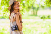 Happy young girl with camera outdoors — Foto Stock