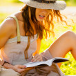 Girl with book sitting on grass — Stok fotoğraf