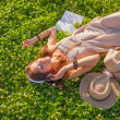 Woman wearing headphones lying on grass — Stock Photo #31253319