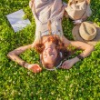 Woman wearing headphones lying on grass — Stock Photo #31253505