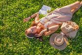 Woman wearing headphones lying on grass — Stock Photo