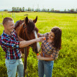 Young couple feeding horse — Stock Photo
