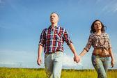 Couple walking through the field — Stock Photo