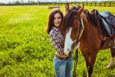 Beautiful woman standing near a horse — Stock Photo