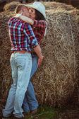 Casal beijando perto de feno — Foto Stock
